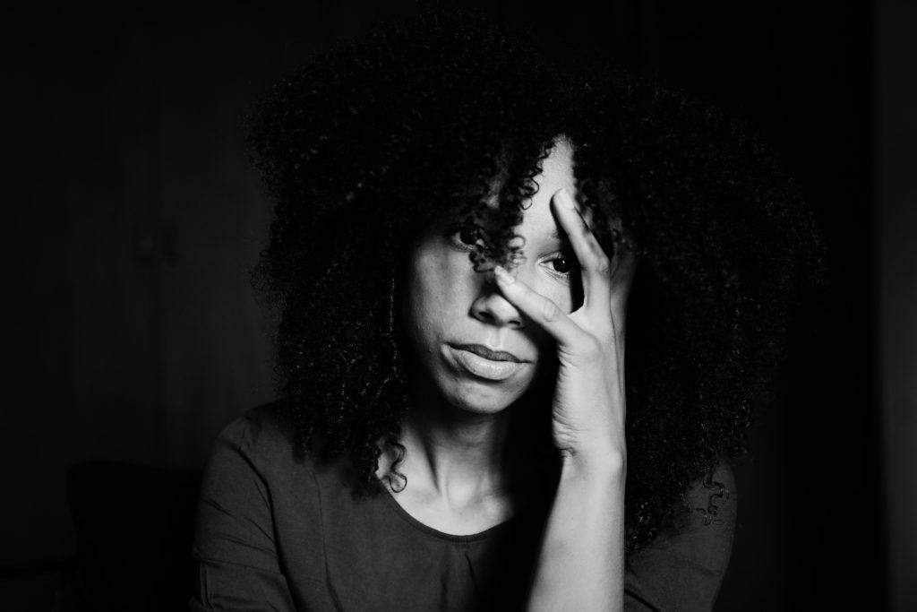 Zwart wit foto van een vrouw die nadenkend door haar handen kijkt