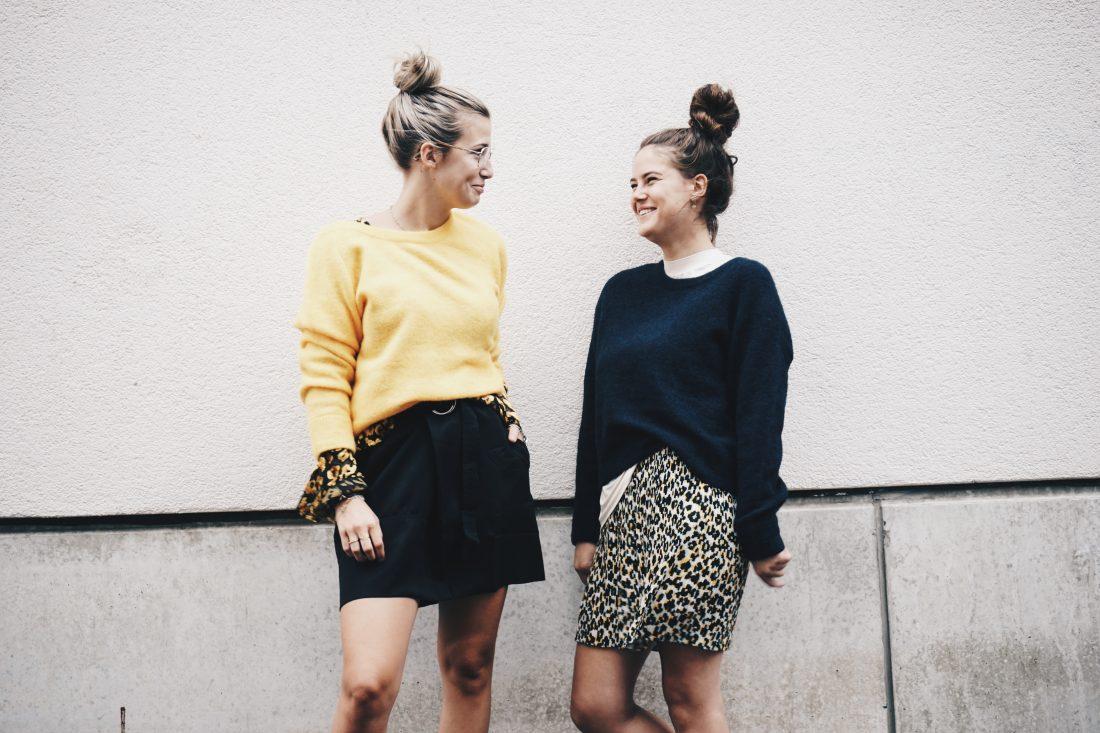 Twee modellen poseren voor een lichte muur