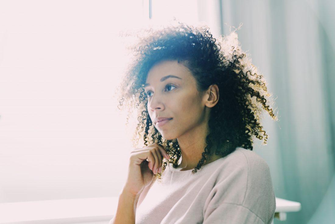 Vrouw met krullen kijkt dromerig