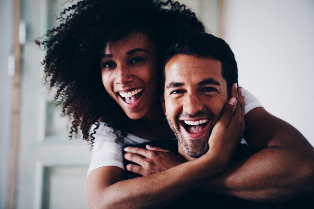 Donker model met krullen hangt op de schouders van een lachende man