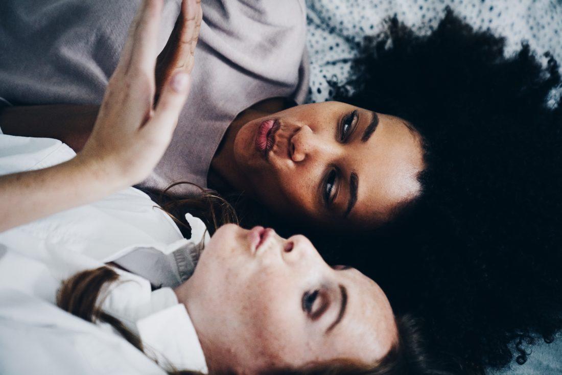 Twee vrouwen op een bed maken een kushand