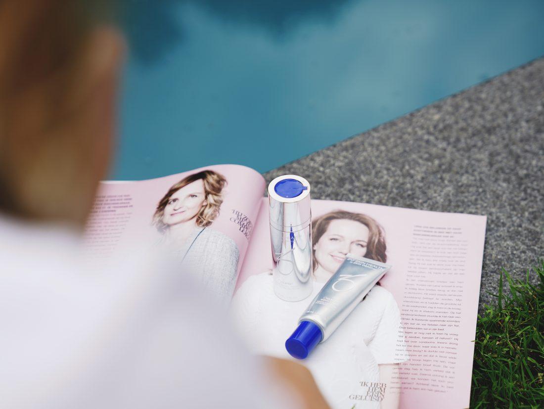 Zonbeschermingsproducten op een magazine aan de rand van het zwembad